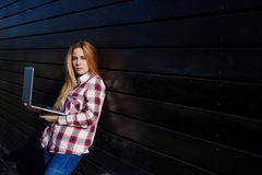 Tragbare Laptop-Computer des jungen modischen Studentengebrauches auf dem Campus lizenzfreie stockfotografie