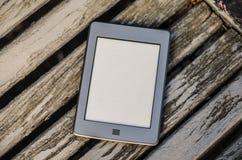 Tragbares elektronisches Buch, das auf einer Bank im Park liegt Lizenzfreie Stockfotos