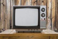 Tragbares Fernsehen und Tabelle der Weinlese mit rustikaler Kabinen-Wand Stockfotos