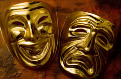 Tragedy and Comedy. Theatrical mask of tragedy and comedy over a grunge brown background Stock Photos