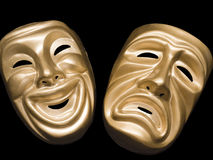 Tragedy and comedy masks on black. Traditional gold masks representing tragedy an comedy in classical theater Royalty Free Stock Photo