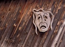 Tragedy theatrical mask. On wooden background Stock Image