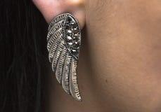 Tragen eines silbernen earing Metallflügels stockbilder