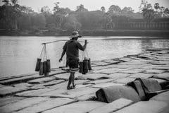 Tragen seiner Waren mit einem Bambuspfosten stockfoto
