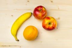 Tragen Sie auf einer Banane des hölzernen Brettes, der Apfel Früchte, orange Stockfoto