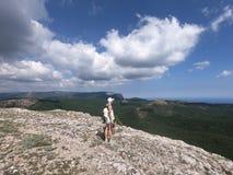 Tragen Sie das Mädchen zur Schau, das auf der Klippe des Berges steht, der Meer, Vogelperspektive betrachtet Stockbild