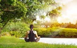 Tragen Sie das Mädchen zur Schau, das im Naturgrünpark bei dem Sonnenaufgang meditiert Lizenzfreie Stockfotos