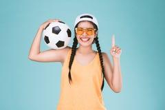 Tragen Sie den Frauenfan zur schau, der einen Fußball hält und Finger des Punktes einer herauf Siegerzeichen feiern Stockfotos