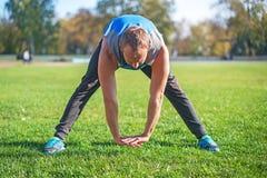 Tragen Sie den Mann zur Schau, der am Park ausdehnt und tun trainiert auf Gras Eignungskonzepte Stockbilder