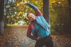 Tragen Sie den Mann zur Schau, der am Parkherbst ausdehnt und Übungen tun Eignungskonzepte Stockbild