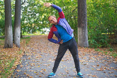 Tragen Sie den Mann zur Schau, der am Parkherbst ausdehnt und Übungen tun Eignungskonzepte Lizenzfreie Stockfotografie