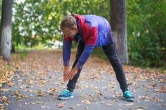 Tragen Sie den Mann zur Schau, der am Parkherbst ausdehnt und Übungen tun Eignungskonzepte Stockfoto