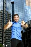 Tragen Sie den Mann zur Schau, der Siegsiegerdaumen oben nach laufendem Training im städtischen Geschäftsgebiet tut Stockbild
