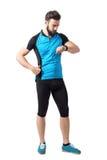 Tragen Sie den Radfahrenathleten im blauen Trikothemd Zeit auf Armbanduhr überprüfend zur Schau Lizenzfreies Stockfoto