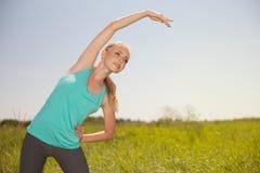 Tragen Sie die blonde junge Frau der Schönheit zur Schau, die im Freienyoga trainiert Lizenzfreie Stockbilder