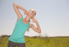Tragen Sie die blonde junge Frau zur Schau, die im Freienyogafoto trainiert Stockbild