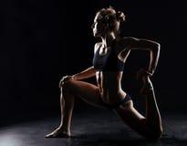 Tragen Sie die Eignungsfrau zur schau, die Yoga auf schwarzem Hintergrund tut Stockbild