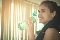Tragen Sie die Frau zur Schau, die Süßwasser beim Trainieren in der Eignung trinkt lizenzfreie stockfotos
