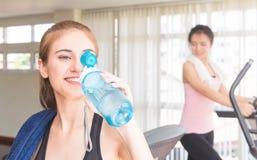 Tragen Sie die Frau zur Schau, die Süßwasser in der Eignungsturnhalle trinkt lizenzfreie stockfotografie