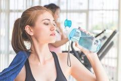 Tragen Sie die Frau zur Schau, die Süßwasser in der Eignungsturnhalle trinkt lizenzfreies stockbild