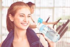 Tragen Sie die Frau zur Schau, die Süßwasser in der Eignungsturnhalle trinkt stockfotos