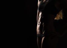 Tragen Sie Eignungsfrau mit den starken Muskeln auf schwarzem Hintergrund zur Schau Stockfoto