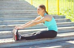 Tragen Sie, Eignungskonzept - die junge Frau zur Schau, die Übungen ausdehnend tut lizenzfreie stockbilder