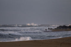 Tragen Sie Fischer auf einem Strand an einem stürmischen Nachmittag zur Schau Lizenzfreie Stockfotografie