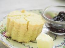 Tragen Sie Formscone mit Butter- und Himbeerstau Stockfotos