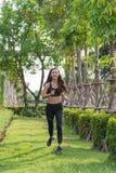Tragen Sie Frauenübung, indem Sie am Park, sie rütteln, laufen auf dem Gras zur Schau lizenzfreie stockfotos