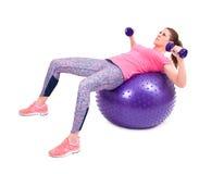 Tragen Sie Frauenübung mit einem pilates Ball und Dummköpfen zur Schau Lizenzfreie Stockfotos