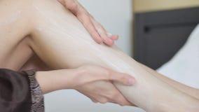 Tragen Sie Fußcreme auf Creme für den Körper auf schönen weiblichen Beinen stock footage