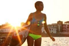 Tragen Sie Mädchen im Bikini auf dem Strand nahe dem Meer, Sonnenuntergangzeit, goldenes Stundenlicht, watersport Lebensstil zur  Stockbilder