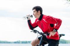 Tragen Sie Mann auf Trinkwasser der Mountainbike auf Rest zur Schau Lizenzfreie Stockfotos