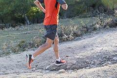 Tragen Sie Mann mit den zerrissenen athletischen und muskulösen Beinen zur Schau, die downhil laufen lassen Lizenzfreies Stockfoto