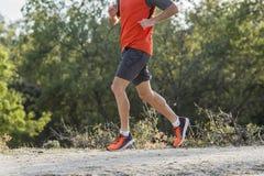 Tragen Sie Mann mit den zerrissenen athletischen und muskulösen Beinen zur Schau, die downhil laufen lassen Stockbilder