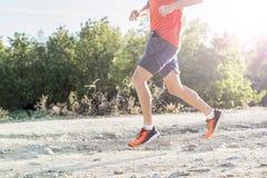 Tragen Sie Mann mit den zerrissenen athletischen und muskulösen Beinen zur Schau, die downhil laufen lassen Lizenzfreies Stockbild