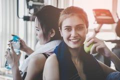 Tragen Sie Trinkwasser der Frauen zur Schau und essen Sie Apfel beim herein trainieren lizenzfreie stockfotografie