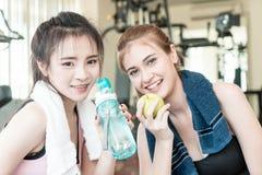 Tragen Sie Trinkwasser der Frauen zur Schau und essen Sie Apfel beim Trainieren in der Eignung stockfotografie