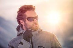 Tragende Anorakjacke des Skifahrermannsonderkommandos mit Sonnenbrilleporträt erforschendes schneebedecktes Land, das mit alpinem lizenzfreie stockfotos
