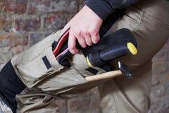 Tragende Arbeit der Arbeitskraft keucht mit Werkzeugen in den Taschen Stockfotos