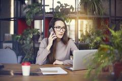 Tragende Augengläser des schönen Mädchens im coworking Studio, das durch Smartphone spricht Konzept von den jungen Leuten, die mi Lizenzfreies Stockfoto