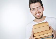 Tragende Bücher des jungen glücklichen Mannes Stockfoto