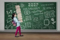 Tragende Bücher des kleinen Mädchens mit Gekritzel an Bord Lizenzfreie Stockfotos