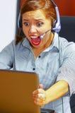 Tragende Bürokleidung und -kopfhörer der jungen attraktiven Frau, die durch den Schreibtisch betrachtet Bildschirm, Ergreifungsla Stockfoto
