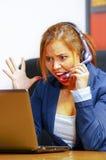 Tragende Bürokleidung und -kopfhörer der jungen attraktiven Frau, die durch den Schreibtisch betrachtet Bildschirm, umgekippten K Stockbilder