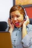 Tragende Bürokleidung und -kopfhörer der jungen attraktiven Frau, die durch den Schreibtisch betrachtet Bildschirm, umgekippten K Lizenzfreie Stockfotografie