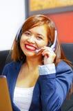 Tragende Bürokleidung und -kopfhörer der jungen attraktiven Frau, die durch den Schreibtisch betrachtet den Bildschirm, arbeitend Stockbilder
