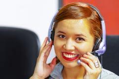 Tragende Bürokleidung und -kopfhörer der jungen attraktiven Frau, die durch den Schreibtisch betrachtet den Bildschirm, arbeitend Lizenzfreie Stockfotos