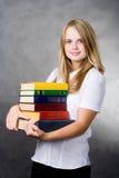Tragende Bücher des Mädchens Stockfotos